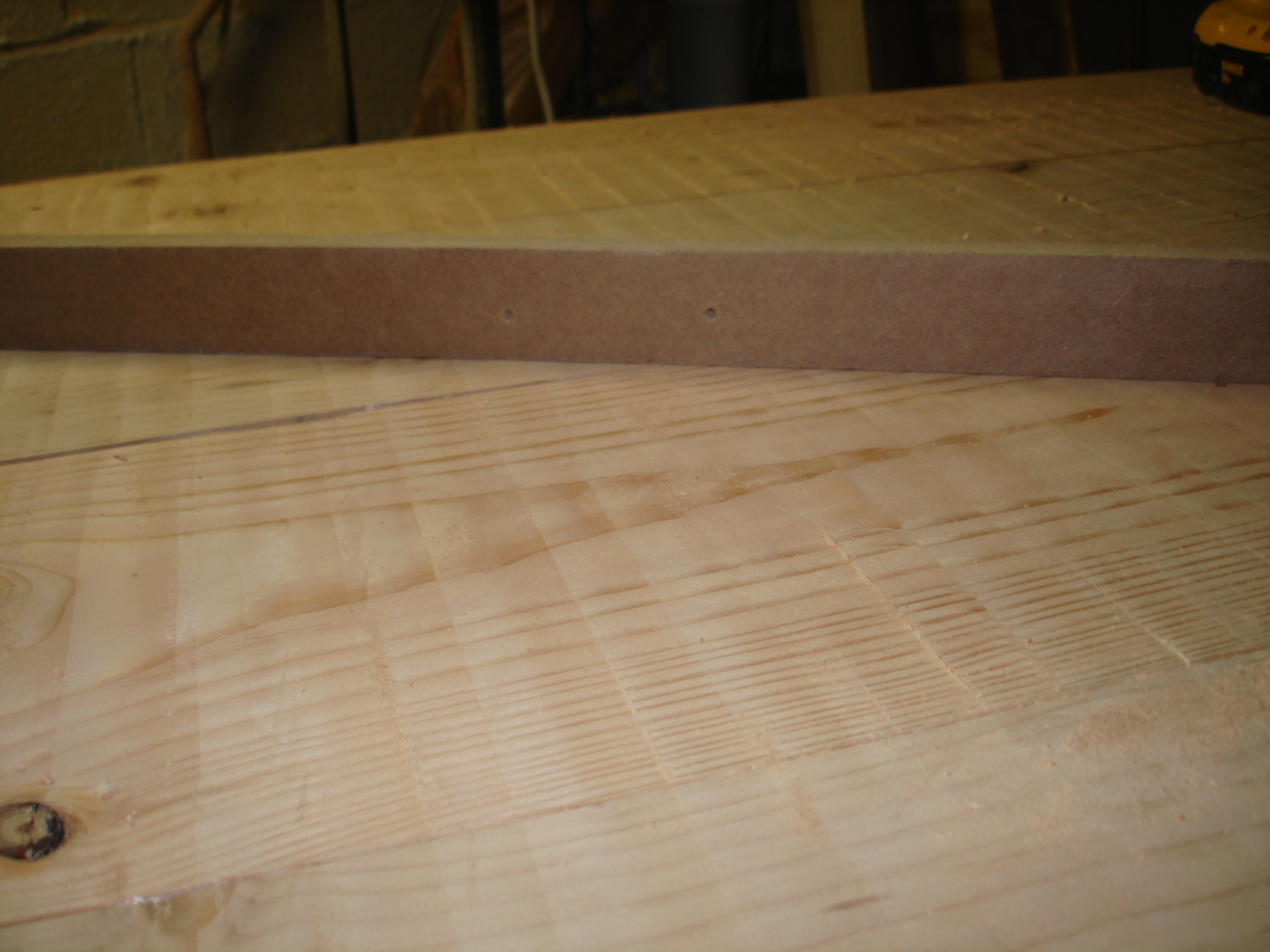 I used the sacrificial guide to check the flatness of the tabletop base after the second pass and was happy with the results.  You can still see the tool marks from the router.  I took a couple of passes with the belt sander to smooth it out, but wasn't too worried about the ridges