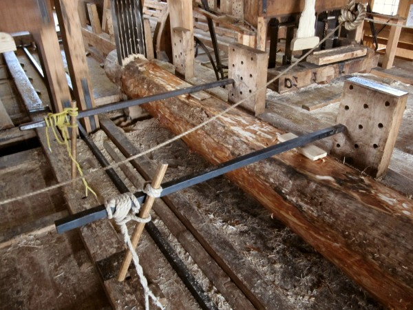 The log to be sawn is affixed to a wooden sled. Which each upward motion of the saw it is pushed 1 mm into the saw blades.