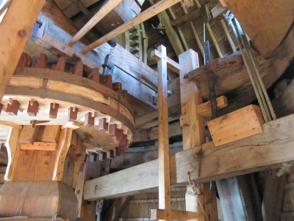 The brake is operated by a giant lever which weight constricts the wooden blocks against the wheel. This lever is operated by the long stick you see coming out the back of the cap on previous pictures.