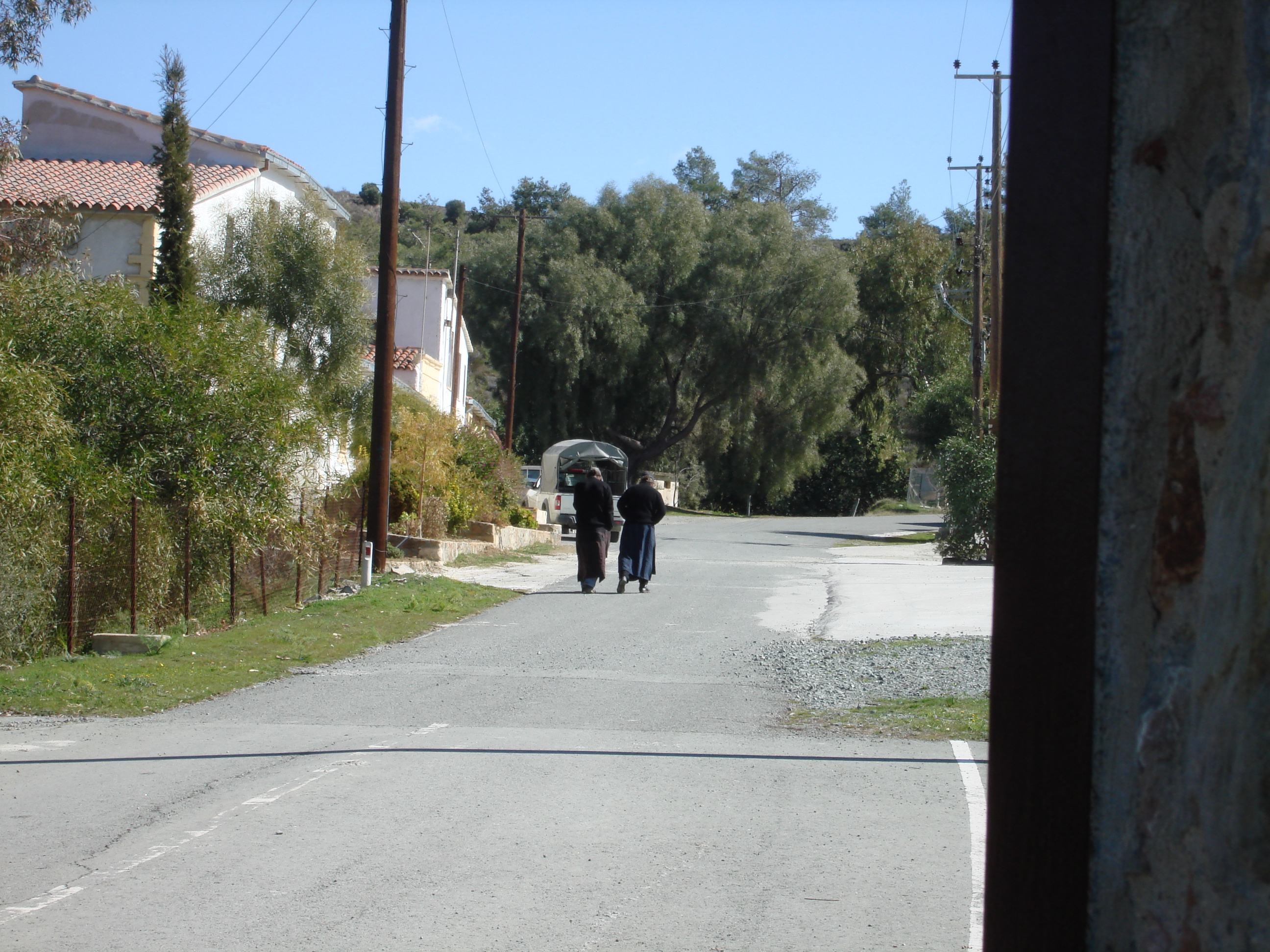 Two monks walk along the entrance to a monestery